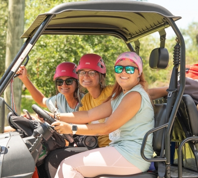 Three Camp Aranzazu activity leaders transporting supplies in golf cart. Photo by: Beyond Memory Photography