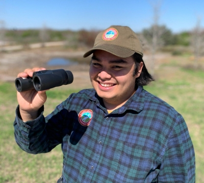 A Camp Aranzazu activity leader, Angel, smiles holding binoculars while wearing the olive camp hat and embroidered flannel.