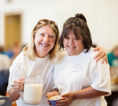 Summer camp volunteer pictured smiling with camper.