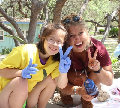 Camper and Amelia make peace sign with fingers and smile at camera during t-shirt tie-dying