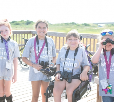 Four campers from Camp MDA smile and show off binoculars in the middle of birdwatching. Photo by: Beyond Memory Photography
