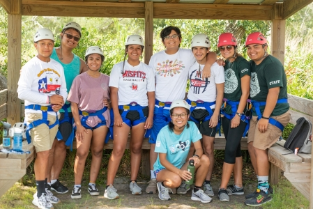 Group of campers from Camp TLC and activity leaders smiling in the shade as they wait to tackle the ropes challenge course. Photo by: Beyond Memory Photography