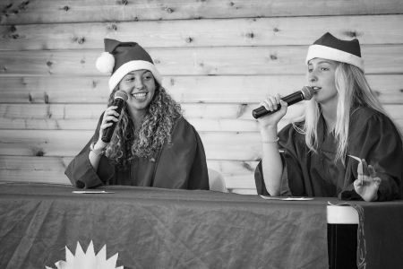 Two activity leaders performing a Camp News Network broadcast wearing Santa hats and graduation robes during meal time. Photo by: Beyond Memory Photography