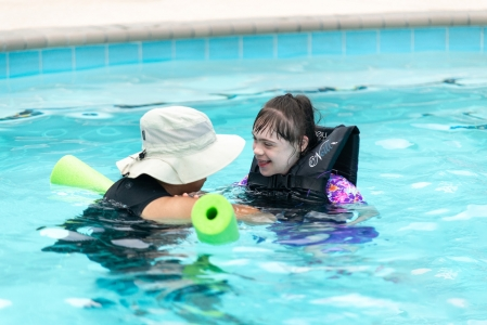 Camper wearing lifejacket smiles and swims up to a partner staff member using a pool noodle. Photo by: Beyond Memory Photography