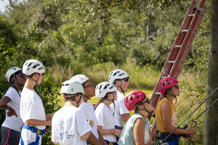Campers and camp staff watch friends scale the rockwall while wearing helmets and harnesses. Photo by: Beyond Memory Photography