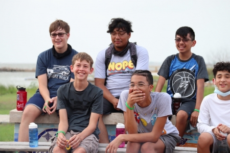 Campers smile and laugh as they tell stories at a campfire on the bayfront