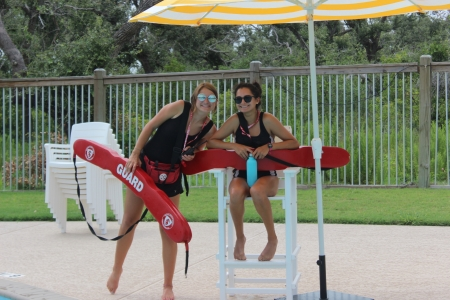 Two activity leaders smile as perform lifeguard duties at one of Camp Aranzazu's pools.