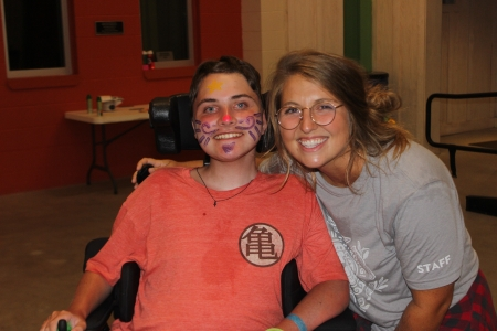 Amelia, Camp Director, smiles with camper as they dance at Camp MDA's dance party.