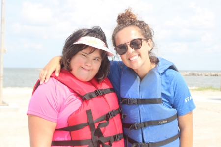 Camper from Camp SOAR smiling with former program manager, Alexa, while they wait at the waterfront for sailing to begin.