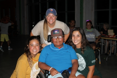 Three activity leaders smile with camper as they dance at Camp MDA's dance party.