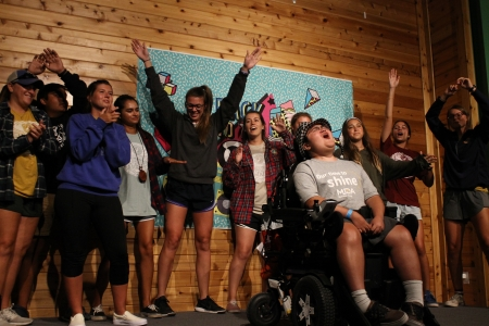 A group of more than 10 activity leaders sing and dance in the background for a camper singing at a MDA Camp's talent show.