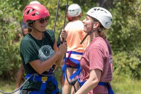 Activity leader gets camper fastened into harness to climb the rockwall Photo by: Beyond Memory Photography