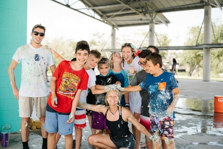 Campers gather around activity leader and smile after a messy and wet game at the plaza