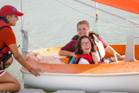 Camper from Camp Aspire smiles before taking off in sailboat with activity leader. Photo by: Beyond Memory Photography