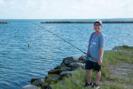 Camper from Camp MDA starting his day off fishing at the bayfront and smiling at the camera. Photo by: Beyond Memory Photography
