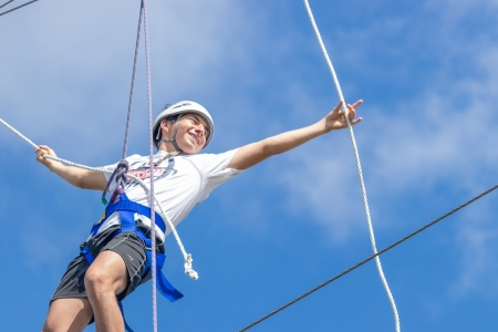 Camper smiles and reaches for the next rope to help him make his way across the tight rope in the challenge course at camp. Photo by: Beyond Memory Photography