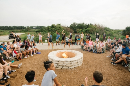 Camp activity leaders dance at evening campfire