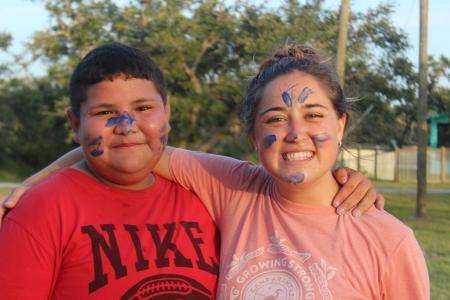 Smiling camper pictured with a Camp Aranzazu summer camp volunteer.