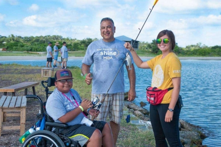 A camper using and wheelchair and support staff member from Camp MDA smile with camp activity leader after catching and reeling in a fish. Photo by: Beyond Memory Photography