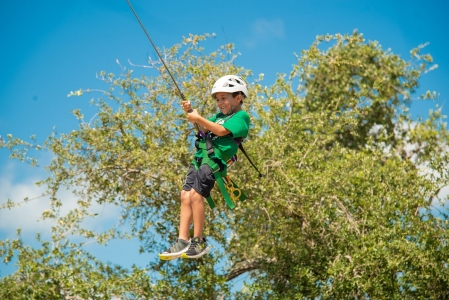 Smiling camper smiling as they make their way down our zipline. Photo by: Beyond Memory Photography