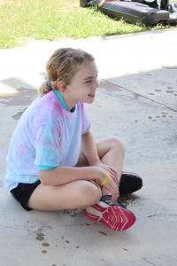 Camper sits criss cross and smiles during a messy game at Camp Aranzazu