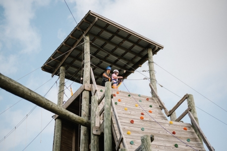 Camper and activity leader look out over the rest of the challenge course after a climb up the rockwall.