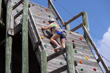 Camper climbs up rockwall at camp