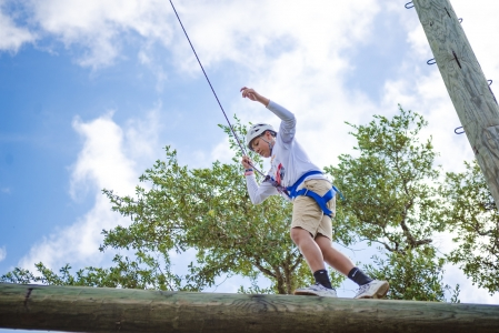 Camper trying to keep his balance while wearing a harness and walking across a long in the challenge course at camp Photo by: Beyond Memory Photography