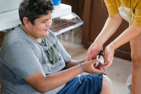 Camp Aranzazu activity leader hands a small rat from the nature hut to a smiling camper Photo by: Beyond Memory Photography