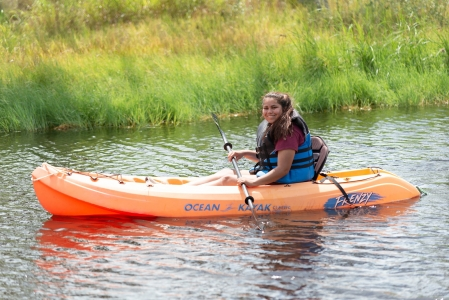 Camper takes a break to smile at camera while kayaking in the pond at camp Photo by: Beyond Memory Photography