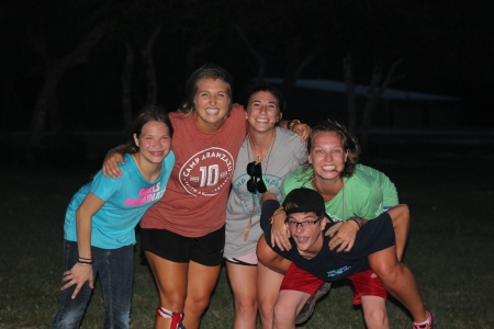 Amelia smiles with other camp staff and campers