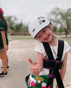 Camper smiling and holding a thumbs up while waiting to scale the rock wall.
