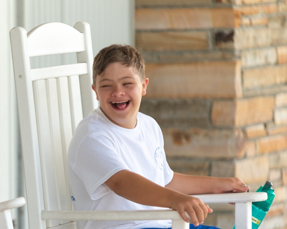 Camper from Camp SOAR enjoying time with friends on our rocking chairs outside of the dining hall. Photo by: Beyond Memory Photography